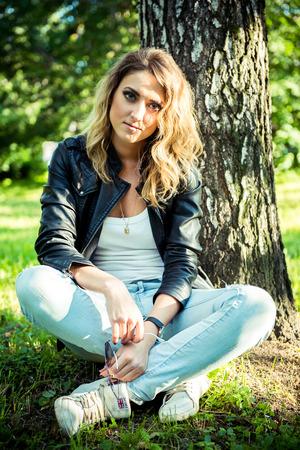 chaqueta de cuero: Hipster hermosa chica en la chaqueta de cuero y pantalones vaqueros. Moda joven posando con chaqueta de cuero