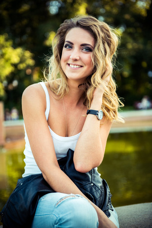 avocation: Hipster beautiful girl in leather jacket and jeans. Fashion girl posing with leather jacket Stock Photo