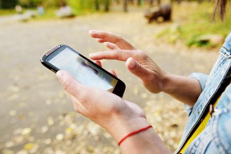 woman on phone: Woman using smart phone outside Stock Photo
