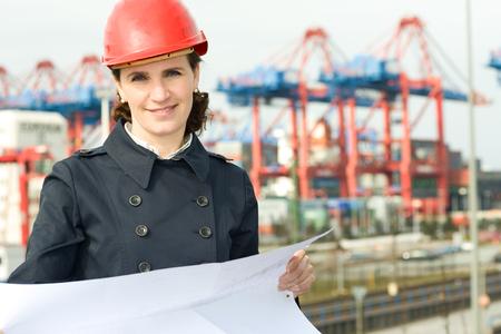 ingeniero civil: Mujer ingeniero civil que lleva el tim�n y el control de los dibujos en frente de la industria de fondo del puerto