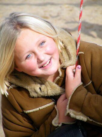 Photo de 8-12 ans, blonde, jeune fille aux yeux bleus sur pneus swing souriant au soleil. Banque d'images - 3829942