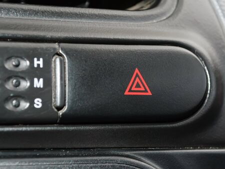 Black rounded emergency button with red triangles