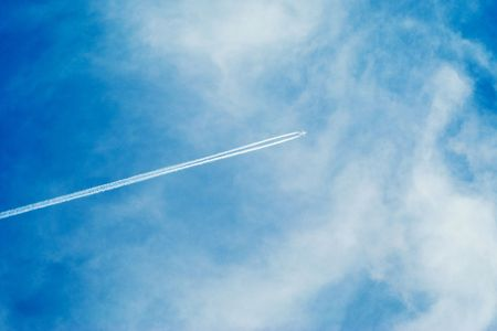 vapor trail from a passenger plane in the blue sky with light clouds