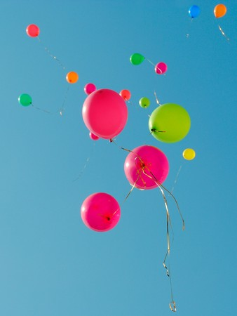 Multi colored baloons flying up in the sky Stock Photo