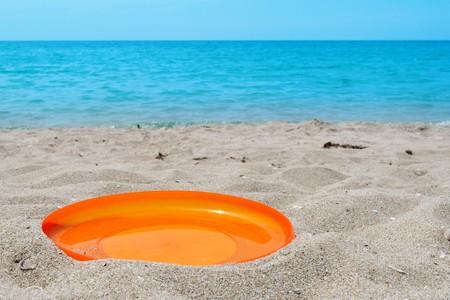 orange frisbee sport disk in sand on beach