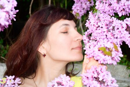 redbud: beautiful young woman sniffs redbud flowers fragrance