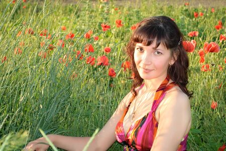 beautiful young woman sits in a poppy field