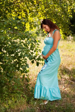 outdoor portrait of beautiful pregnant woman holding her belly photo
