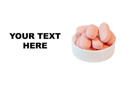 Pile of pink pills in the lid. Isolated on white background  Stock Photo
