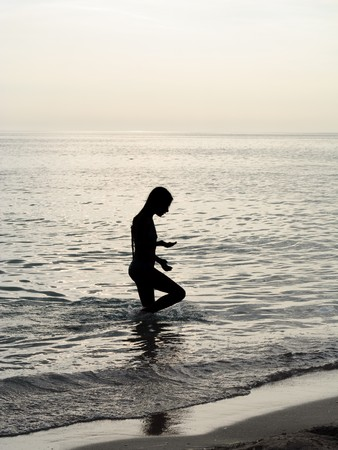 Silhouette of young little girl searching something in the sea