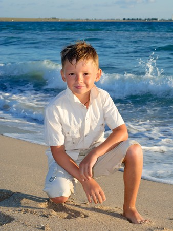 Portrait of a little smiling boy standing at the beach 版權商用圖片
