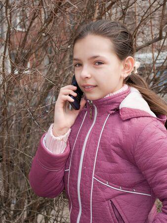 Beautiful teen girl on phone outdoor portrait  Stock Photo