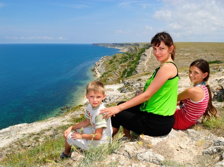 Mother and children sitting on the edge of a clif at the seaside  photo