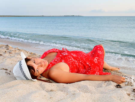Portrait of a beautiful young woman in a red dress and hat on the beach  Stock Photo