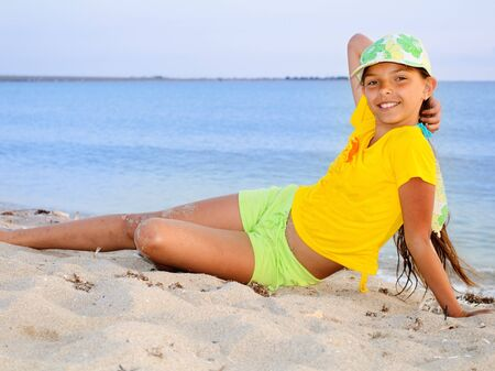 Portrait of a beautiful teenage girl in yellow at the beach  Stock Photo