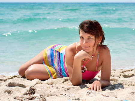 Portrait of a beautiful young woman in a colorful dress on the beach  Stock Photo