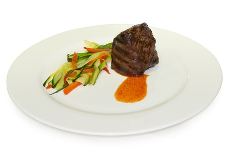 Gourmet fillet steak with vegetables on the white plate. Isolated on white background with clipping path.