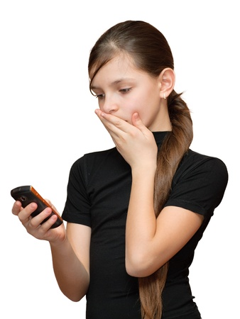 Surprised teen girl looking at the mobile phone in her hand. Isolated on white background. Stock Photo - 8650435