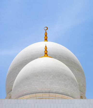 abudhabi: White domes of mosque with golden spiers over the blue sky  Abu-Dhabi, UAE Stock Photo