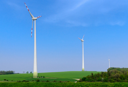 Three wind power generators on the green meadow