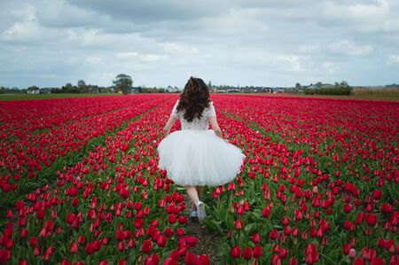 Young woman is enjoying flower fields in Holland