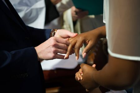White skin man and black skin woman are getting married in a church