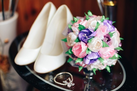 White shoes, bouquet and bride decoration on a glass table
