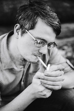 A man in glasses lights a cigarette, black and white