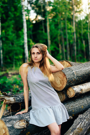Girl in a blue dress near a fallen tree on a background of a forest in summer weather, a wooden spittle of a tree