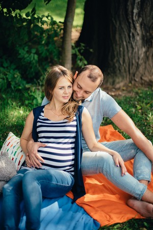 Man and pregnant woman, in an amorous couple in the park