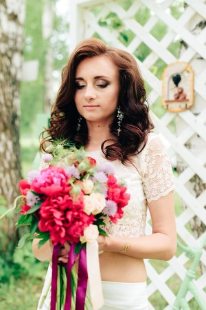 Bride in a beautiful dress in the decor in a summer park 1