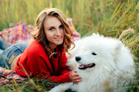 young girl in a nature park hugging a white dog Samoyed Laika at sunset 1