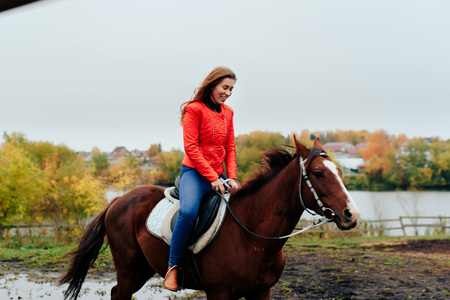 beautiful girl rides a horse in a village in the fall 1 Stock Photo