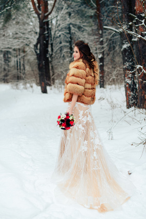 Beautiful bride in a fur coat in a winter pine forest with a wedding bouquet
