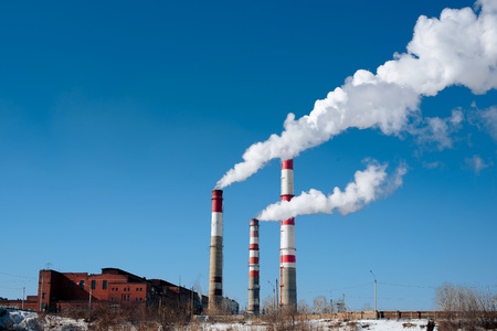 factory pipes with white smoke near the river in winter 1