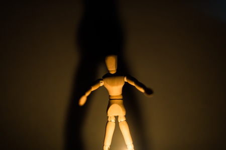 wooden doll on a black background in the light of a candle in a jar 1