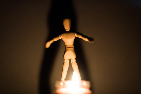 wooden doll on a black background in the light of a candle in a jar