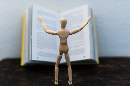 wooden toy in the image of a man on the background of a book Stock Photo