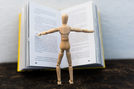 wooden toy in the image of a man on the background of a book Foto de archivo