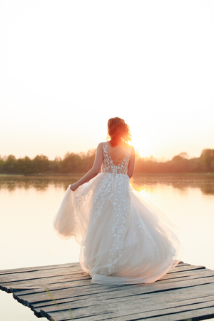 young beautiful bride in white dress on wooden pier near water at sunset 1 Stock Photo