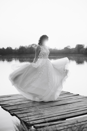 young beautiful bride in white dress on wooden pier near water at sunset 1 Reklamní fotografie