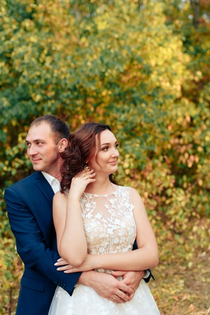 young bride and groom in autumn Park with yellow leaves