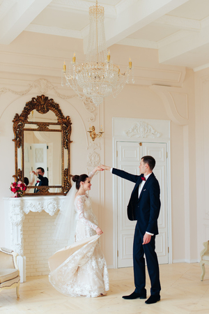 newlyweds in the apartment, a beautiful bride and groom in the rich interior