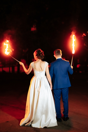 beautiful young newlywed couple with fire torches in their hands and fireworks