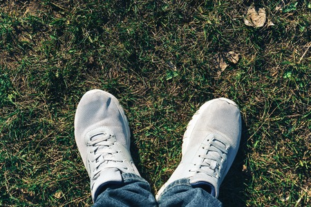 white sneakers on green grass top view
