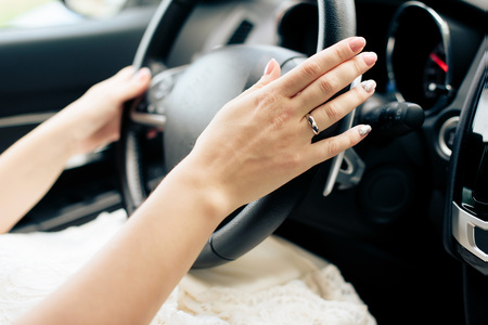 girl's hands on the wheel of a car