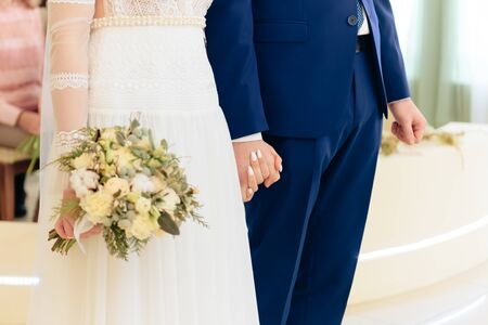 bride with a bouquet of flowers holds the hand of the groom Stock Photo