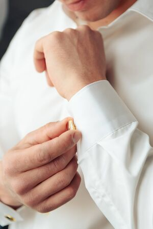 a man in a white shirt fastens his cufflink