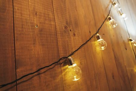 a garland of incandescent bulbs on the wall