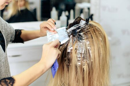stylist's work with the hair of a girl in a beauty salon